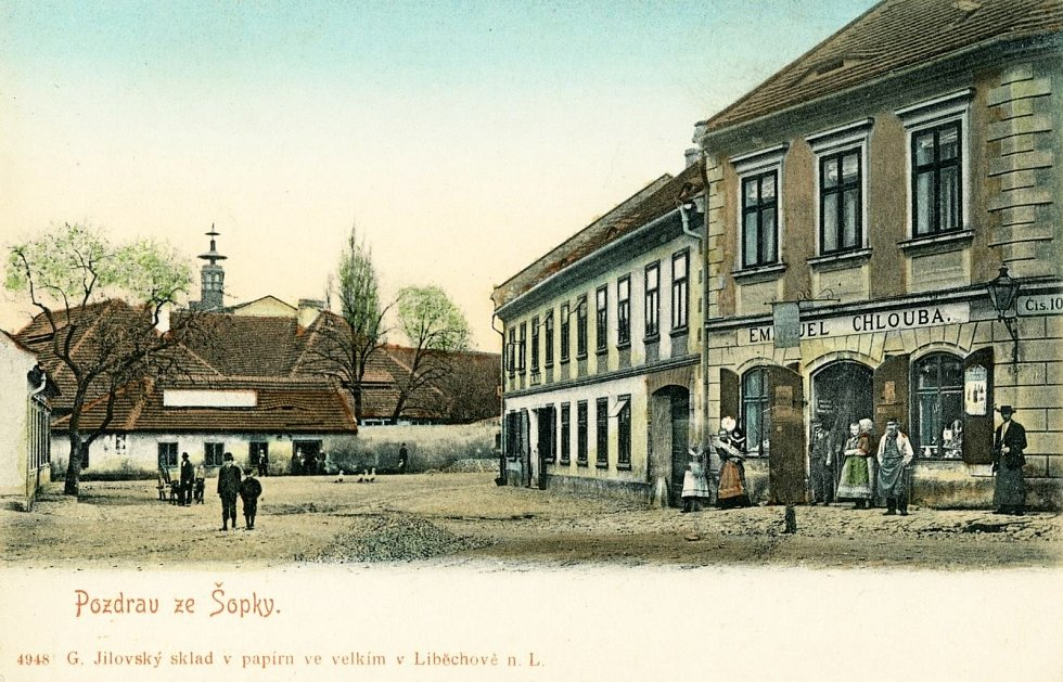 Pšovka. Ulice Legionářů a Bezručova. Kolorovaná pohlednice z roku 1904. V pozadí snímku je bývalý panský dvůr a pivovar. V domě po pravé straně je dnes prodejna jízdních kol Derfl. V sousedním domě s průjezdem byl hostinec U Šimáčků.