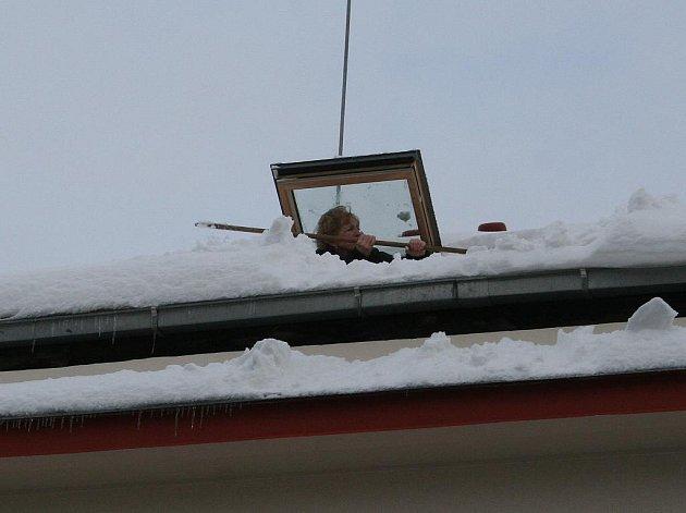 Lidé uklízejí sníh ze střech.Ilustrační foto