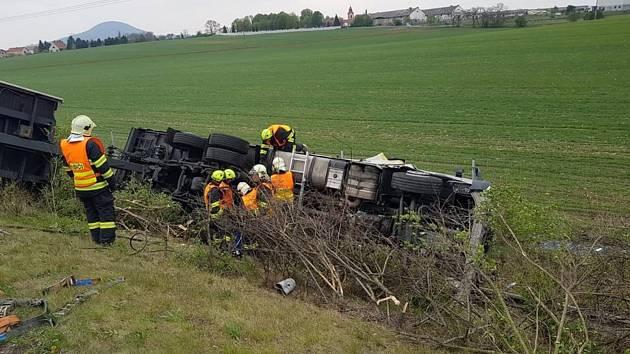 Kamion skončil svoji jízdu na boku mimo dálnici.