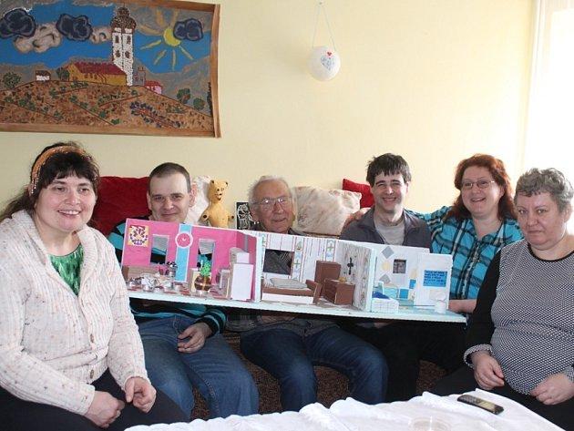 Klienti Slunečnice (první zleva, první a třetí zprava) spolu s pracovnicí stacionáře Marií Bendíkovou (druhá zprava) vyrobili kouzelný domeček. Na snímku jsou spolu s přáteli, kteří je navštívili.