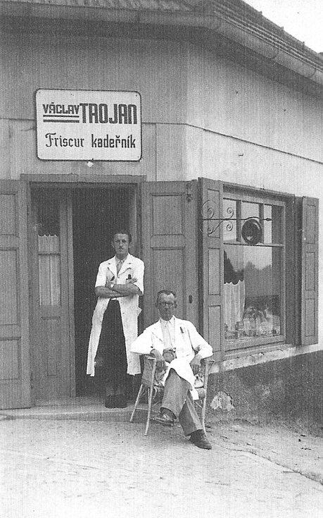 Na černobílé fotografii z roku 1942 je zobrazen vstup s výkladcem do kadeřnictví pana Václava Trojana. Dům stojí na začátku silnice vedoucí k mostu od Vrázovy vyhlídky vedle bývalého hostince U Hanušů. Dnes je zde Autoelektrika p. Brynycha. Na snímku jsou