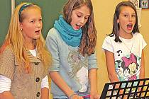 Zpěvačky ze šesté třídy všetatské základní školy (zleva) Eliška Chvojková, Michaela Valentová, vnučka kapelníka známé Přívoranky, a Martina Drdová, které patří do školního týmu, který společně zpívá při slavnostních příležitostech.