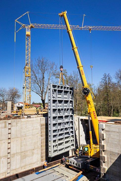 Usazování nových vrat do zdymadla v Hořínském plavebním kanálu u Mělníka. Montáž vrat probíhala pomocí autojeřábu, který byl umístěn na nákladní lodi a vrata zdvihal.