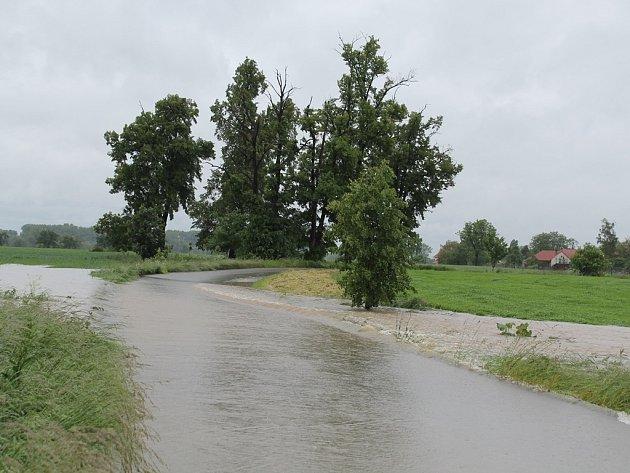 Silnice od Křivous k Vojkovicím, voda se valí přes vozovku.