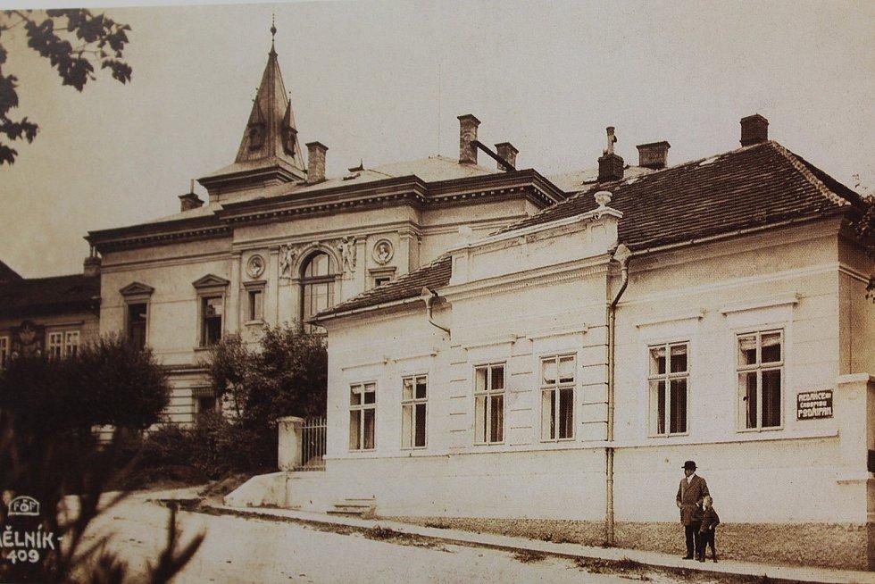 """Ulice Legionářů. Vpravo na domě visí cedulka s nápisem """"Redakce časopisu Podřipan"""". Vlevo za stromy je mezi okny velká cedule """"Jsf. Victorin"""". Uprostřed se nachází s věžičkou vila sv. Julie, postavená v roce 1889. Snímek je datován rokem 1915."""
