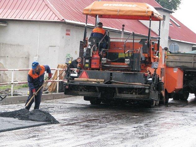 SILNIČÁŘI dělají nový asfaltový povrch silnice. Od úterka by tudy už mohly jezdit auta.