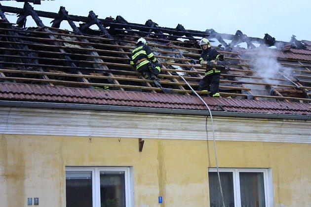 Podkrovní byt v domě na Okrouhlíku v noci vyhořel. Hasiči museli zachraňovat matku s dítětem oknem na terase.