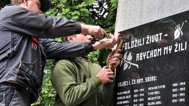 Pracovníci Kamenictví Kalus z Halenkova montují novou žulovou pamětní desku a státní znak na památník obětem II. světové války v Huslenkách na Vsetínsku. Původní mosaznou desku ukradl neznámý zloděj; Huslenky, pondělí 25. května 2015.