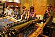 Pracovnice Moravské gobelínové manufaktury ve Valašském Meziříčí vyzvedávají na postřihávací stroj koberec určený pro Ústavní soud v Brně.