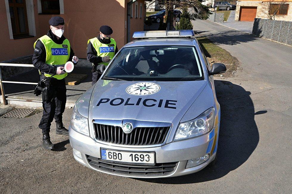 Policejní hlídka v souladu s nařízením vlády kontroluje v pondělí 1. března 2021 ve Valašských Příkazech řidiče mířící mimo okres Vsetín.