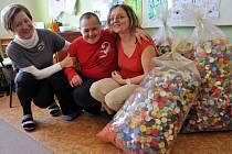 Patnáctiletý Petr Žlebek s ředitelkou ZŠ a MŠ Turkmenská ve Vsetíně Dagmar Šimkovou (vlevo) a její zástupkyní Vlastou Kovářovou (vpravo) a víčky z PET lahví, které pro speciální školu nasbírali zdravotníci a pacienti nemocnice ve Vsetíně.