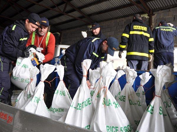 Dobrovolní hasiči zKrhové připravují naplněné pytle spískem, které budou vobci sloužit jako protipovodňové zábrany; Krhová, pátek 16.května 2014.