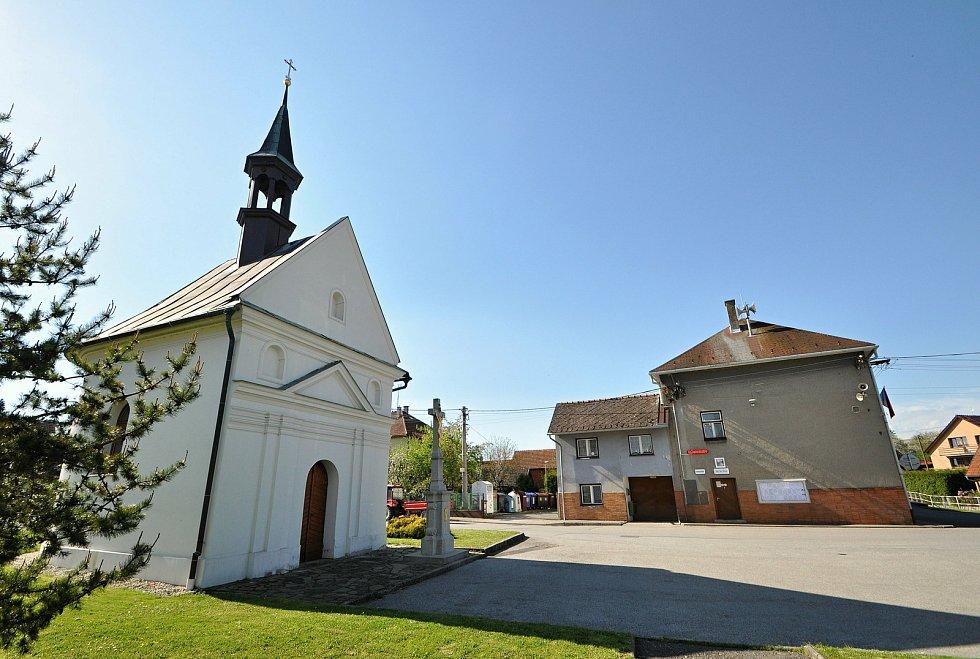 Pohled na náves v Kladerubech. Vlevo je kaple Panny Marie, vpravo budova obecního úřadu.