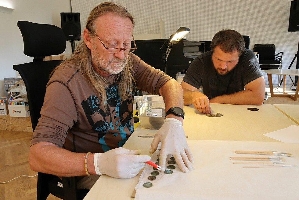 Konzervátor Muzea regionu Valašsko Zdeněk Hanáček (v brýlích) a muzejní archeolog Samuel Španihel zkoumají nález několika stovek stříbrných pražských grošů ze 14. století nalezených v lese v Ústí u Vsetína.
