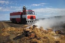 Hořící sběrací lis slámy zapálil strniště