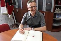 Odcházející farář Kamil Obr se zapisuje do pamětní knihy Města Rožnov pod Radhoštěm. Po sedmi letech odchází z rožnovské farnosti do zlínského kostela.
