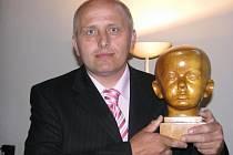 """Igor Špetík drží v rukou svoji dětskou bustu, kterou z třešňového dřeva vyřezal jeho otec Ambrož. """"Modelem jsem mu nejspíše neseděl. Většinou tvořil zpaměti,"""" tvrdí Igor."""