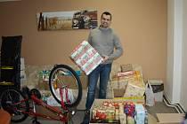 Lukáš Diatka ukazuje nashromážděné vánoční dárky a nazdobený vánoční stromek v dětském domově