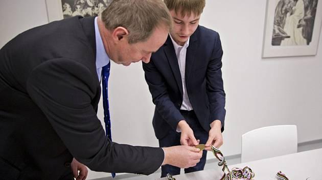 Student Gymnázia Rožnov Jonáš Vala ukazuje krajskému radnímu Petru Gazdíkovi bohatou sbírku medailí z MS v Berlíně.