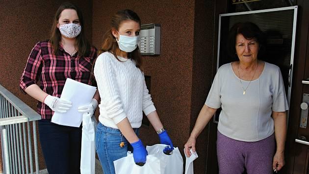 Studentky Eliška Skýpalová (v bílém svetru) a Karolína Knápková se během první vlny koronavirové epidemie zapojili ve Valašském Meziříčí do distribuce ochranných pomůcek seniorům.