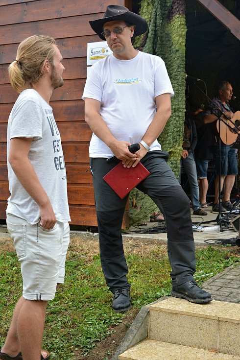 Téměř tři stovky věrných návštěvníků přijely 27. července 2019 i přes uplakané počasí na Pulčín na 24. Amfolkfest. Moderátor festivalu Jan Gottfried.