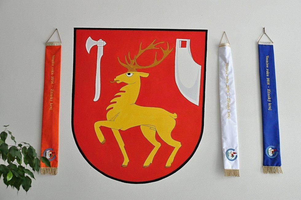 Obec Hošťálková. Obecní znak a stuhy za úspěšnou účast v soutěžích Vesnice roku.