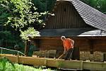 Pracovník Valašského muzea v přírodě v Rožnově pod Radhoštěm čistí nově zbudované dřevěné koryto náhonu, který přivádí vodu k objektu pily z Velkých Karlovic v areálu Mlýnské doliny; pondělí 18. května 2020.