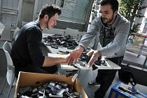 Organizátoři veřejné sbírky nazvané Malý pokus o pomoc – Jan (v černém) a Martin Kubíkovi ze Vsetína – sčítají staré mobilní telefony, které lidé ve Vsetíně za měsíc trvání uvedené sbírky odevzdali na čtyřech sběrných místech.