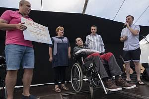 Ředitel Resortu Valachy Tomáš Blabla předává symbolický šek na 100 tisíc korun Jakubu Horákovi a jeho rodičům.