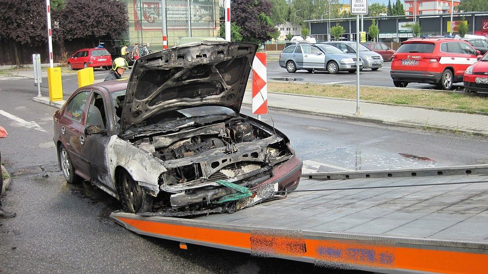 Hasiči nakládají v pátek 19. července 2019 odpoledne před nákupním centrem ve Valašském Meziříčí na vůz odtahové služby vrak osobního vozu Škoda, který zničil požár.