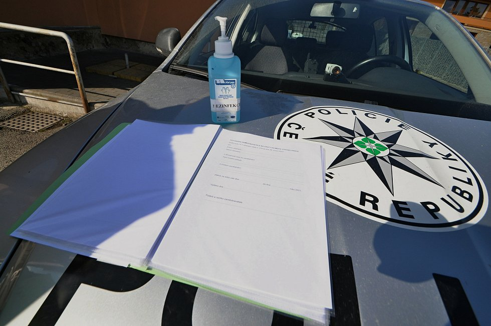 Policejní hlídka kontroluje v pondělí 1. března 2021 ve Valašských Příkazech řidiče mířící mimo okres Vsetín. Ve výbavě policistů nechybí dezinfekce, k dispozici mají i formuláře potřebné při cestách mimo okres, které mohou poskytnout motoristům.