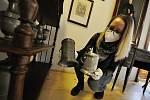 Kristýna Pončíková, lektorka Muzea regionu Valašsko, ukazuje původní cínové nádobí vystavené na Zámku Lešná - například cechovní poháry či cínovou slánku.