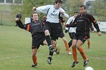 Na snímku bojují o míč s hostujícím obráncem Pavel Drda, Michal Kramoliš a Milan Drda (odleva).