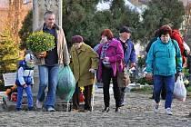 Lidé přinášejí květiny a zapalují svíčky na hřbitově v Novém Hrozenkově, sobota 31. října 2015
