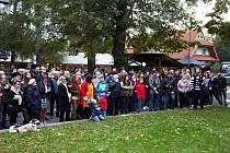 Diváci sledují umělecký happening v ulici mezi Brillovkou a restaurací Brasserie Avion v Rožnově pod Radhoštěm, která nově nese jméno umělce Maria Kotrby; 4. října 2019