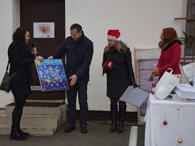 Na fotografii zástupkyně Handicapu Ludmila Sedláčková předává generálnímu ředitel HP TRONIC Danielu Večeřovi poděkování za finanční dar – originální obraz od klientů sdružení.
