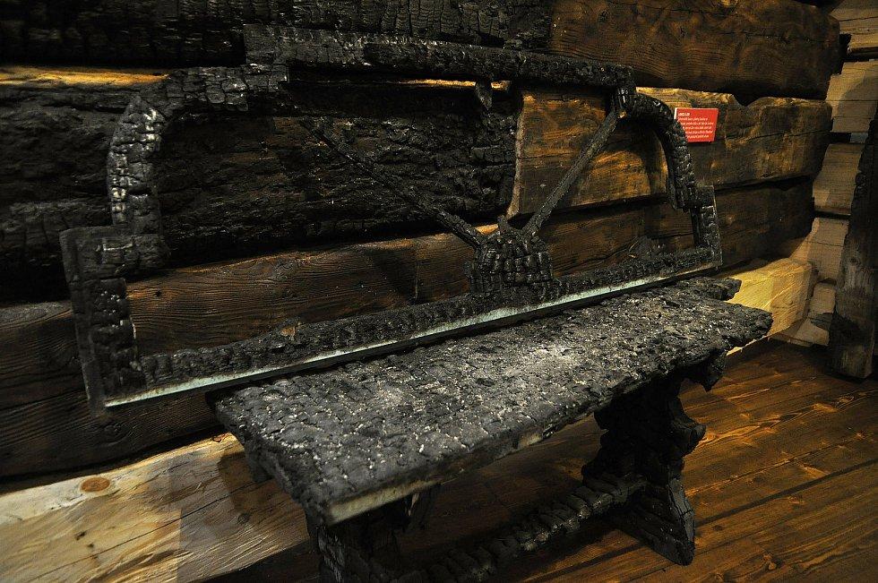 Zuhelnatělá lavice z jídelny Libušín vystavená v Sušáku ve Valašském muzeu v přírodě. Dochovala se proto, že stála u zdi. Byla tak na okraji požářiště, kde byl žár o něco slabší; Valašské muzeum v přírodě v Rožnově, Sušák, 1. patro, srpen 2020