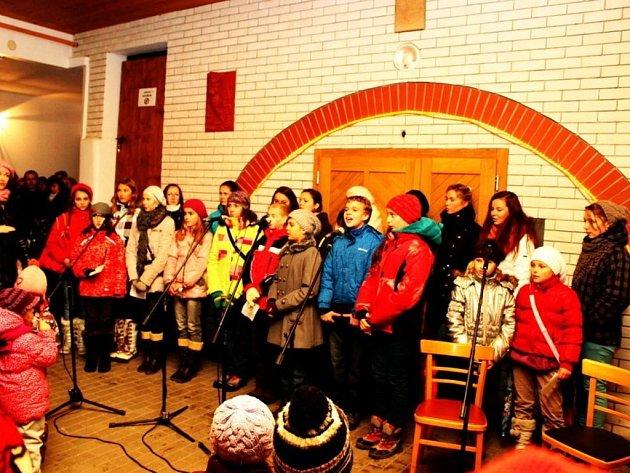 Déšť zahnal zpívající děti i dospělé do zastřešeného dvorního traktu polešovické radnice.