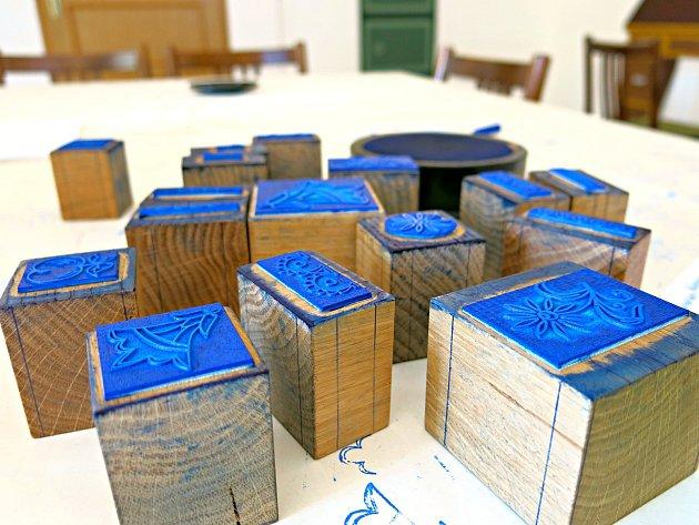 V dílně si mohou turisté vyrobit originální pohlednice pomocí sedmnácti razítek, které věrně napodobují modrotiskové motivy.