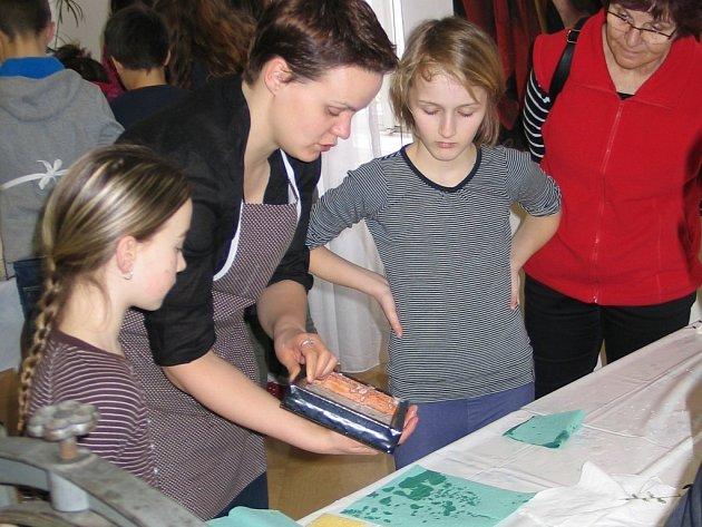 Do výroby ručního papíru děti zasvěcuje restaurátorka Anna Čechová.