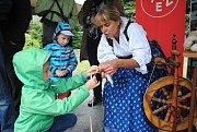 Jitka Dvorská z Valašského Meziříčí (v kroji) předvádí předení na kolovrátku a výrobu papučí a rukavic z ovčí vlny na Bartolomějském hodovém jarmarku ve slovenské Čadci; neděle 26. srpna 2018