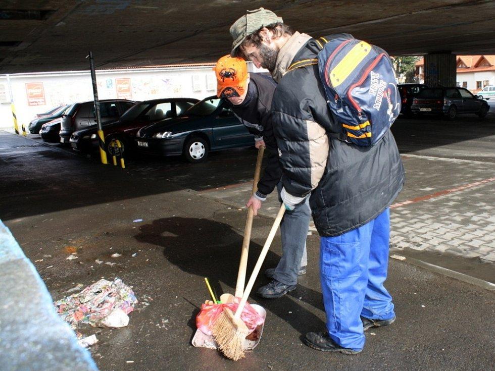 Pracovníci veřejné služby a veřejně prospěšných prací uklízejí odpadky, které se objevily po roztátí sněhu.