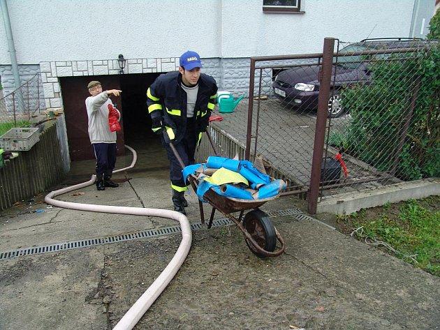 Hasiči pomáhají vyklízet lidem věci ze zatopených sklepů.