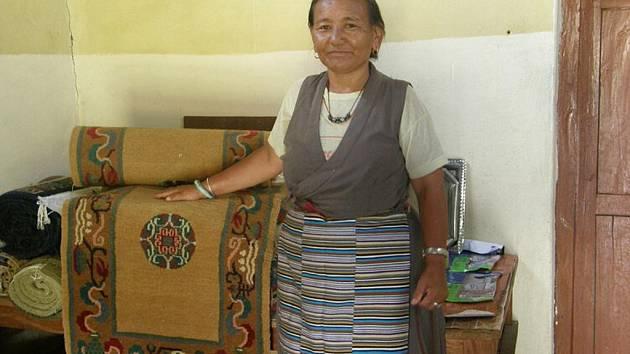 Tradiční tibetský kroj a ručně vyráběný koberec