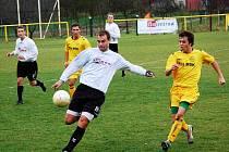 Karlovjané (žluté dresy) se v posledním letošním zápase představili v Ostrožské Nové Vsi, kde uhráli remízu 1:1. Na snímku bojuje o míč Pavel Škrobák s domácím obranou.