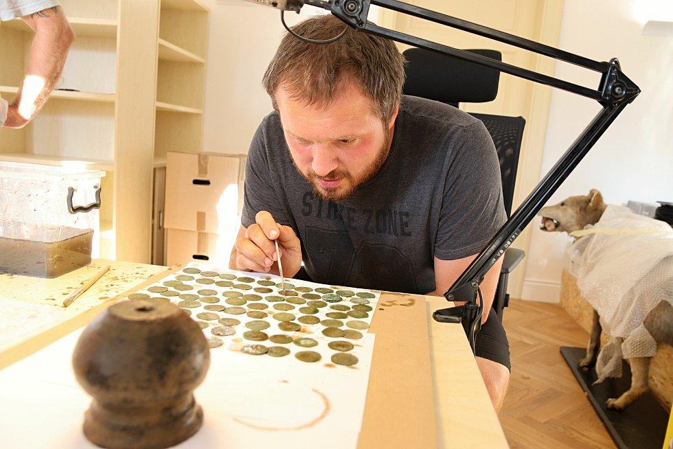 Archeolog Muzea regionu Valašsko Samuel Španihel zkoumá nález několika stovek stříbrných pražských grošů ze 14. století nalezených v lese v Ústí u Vsetína.