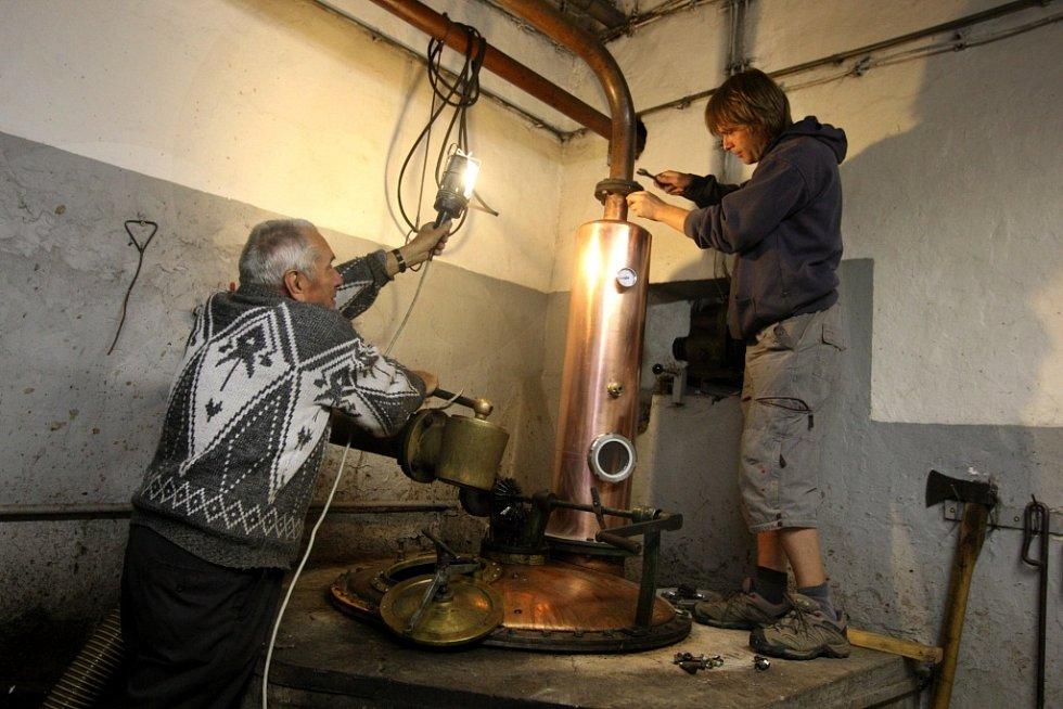 Pálenice v Hovězí. Na snímku František a Michal Kovářovi opravují kotel.