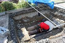 Dělníci opravují prasklé potrubí na horkovodní síti. Trubky jsou staré padesát let a jsou vedené kanálem z betonového profilu.