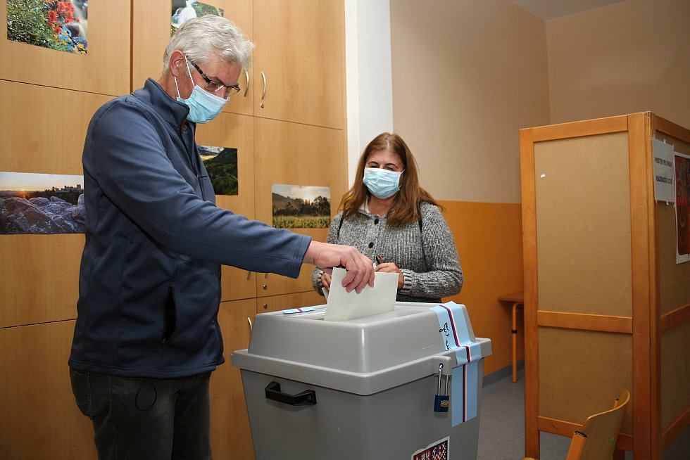 Voliči odevzdávají své hlasy do krajského zastupitelstva ve volební místnosti v Luhu, 2. října 2020.
