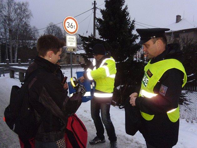 Policisté na Valašsku kontrolovali, zda chodci nosí na oblečení reflexní prvky. Kdo žádný neměl, dostal svítící proužek.